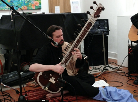 Sitarist Cliff Winnig sitting and playing the sitar in front of a microphone